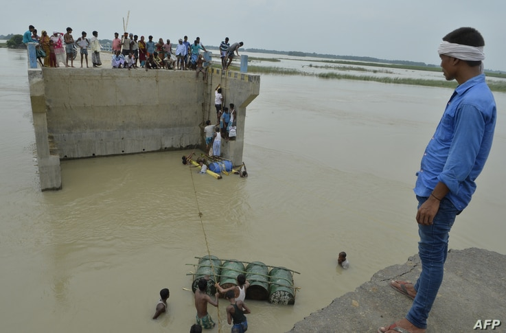 Indian villagers attempt to cross flood waters with the help of rope and empty canisters next to a washed away portion of a bridge at Palsa village in Purnia district in Bihar state.
