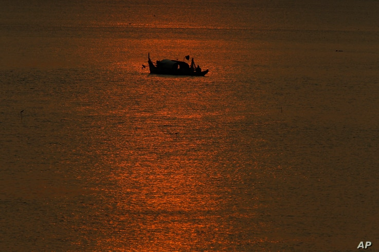 FILE - Cambodian fishermen catch fish in the middle of Mekong river, near Phnom Penh, Cambodia, March 7, 2018.