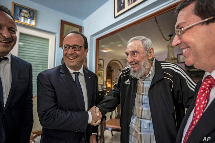 Cuba's former leader Fidel Castro, second right, shakes hands with French President Francois Hollande, while accompanied by Cuba's Foreign Minister Bruno Rodriguez, right, and an unidentified person, left, in Havana, Cuba, Monday, May 11, 2015. Holla...