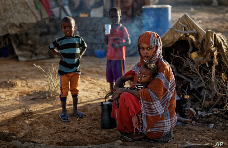 In this photo taken Thursday, March 9, 2017, Fatima Ali and her children, who fled the drought, sit by their makeshift hut in a camp for the displaced in Qardho in Somalia's semiautonomous northeastern state of Puntland.