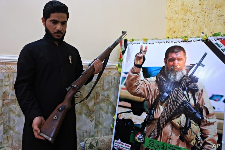 FILE - Talib, the son of Iraqi sniper Ali Jayad al-Salhi, 65, a volunteer with Popular Mobilization Forces killed fighting Islamic State militants, poses with a weapon next to his father's poster in his home in Basra, Iraq, Dec. 5, 2017.