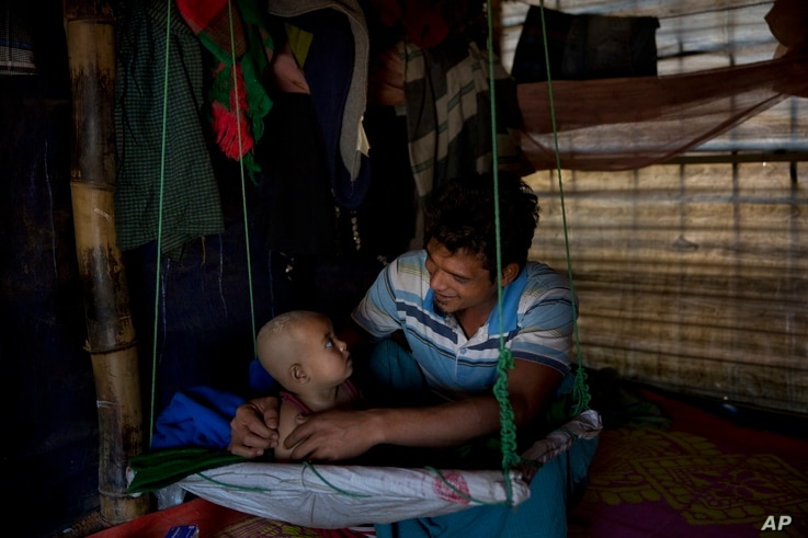 Rohingya Muslim refugee Noor Kadir, 24, from the Myanmar village of Gu Dar Pyin, plays with his son inside the family makeshift shelter in Balukhali refugee camp, Bangladesh, Jan. 21, 2018.