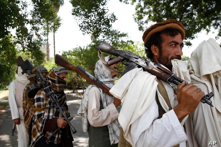 FILE - In this Sunday, July 31, 2011 file photo, Taliban fighters hold their heavy and light weapons before surrendering them to Afghan authorities in Jalalabad, east of Kabul, Afghanistan.