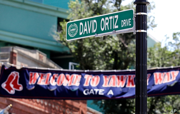 """A new """"David Ortiz Drive"""" street sign is posted outside Fenway Park, after a ceremony where part of Yawkey Way was renamed, June 22, 2017, in Boston. Ortiz's No. 34 was retired in a ceremony prior to a game later that day."""