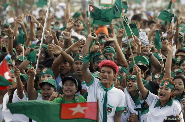 Supporters wave flags during Union Solidarity and Development Party (USDP) campaign rally in Yangon, Nov. 6, 2015.