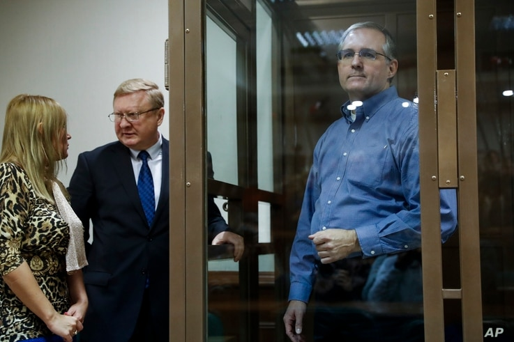 Paul Whelan, a former U.S. Marine, who was arrested in Moscow at the end of last year, right, looks through a cage's glass as his lawyers talk to each other in a court room in Moscow, Russia, Jan. 22, 2019.