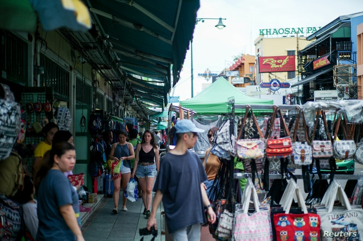 Tourists walk past street vendor shops at the Khao San tourist street in Bangkok, Thailand, Aug. 1, 2018.