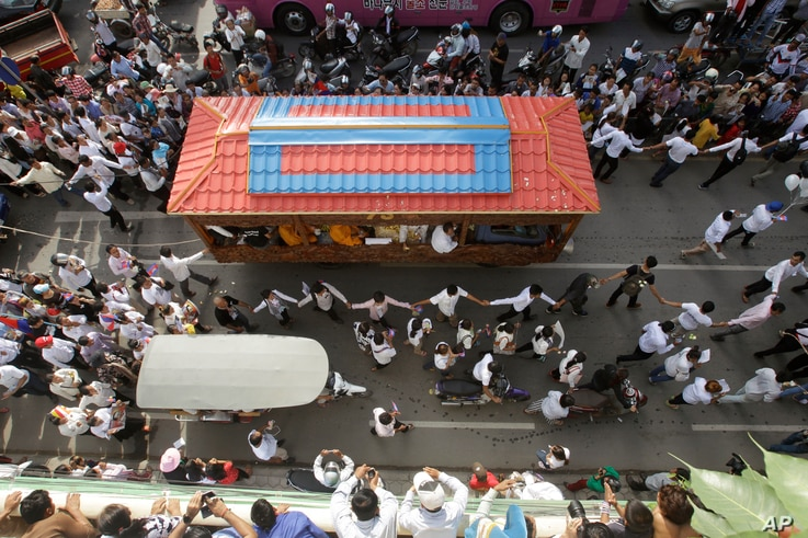 FILE - Mourners march along the decorated vehicle loaded with the body of Cambodian prominent political analyst Kem Ley during a funeral procession in Phnom Penh, Cambodia.