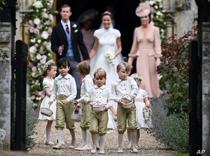 FILE - Britain's Prince George, foreground center, reacts after the wedding of his aunt, Pippa Middleton to James Matthews, at St Mark's Church in Englefield, England on May 20, 2017.
