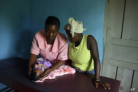 A maternal and child health aide, left, examines a newborn baby at a clinic in Pendembu, Kailahun district, Sierra Leone