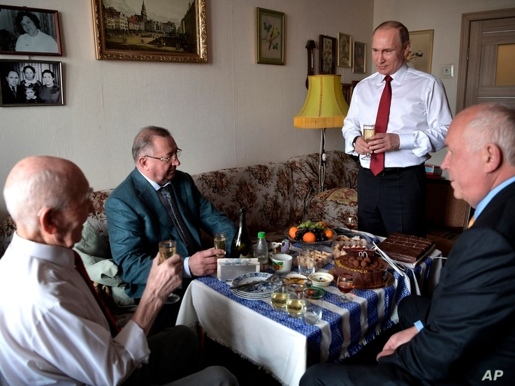 FILE - Russian President Vladimir Putin, second right, makes a toast to congratulate former head of the KGB intelligence group in Dresden, Germany, Lazar Matveyev, left, on his 90th birthday on the eve of Victory Day, in Zhulebino in Moscow, Russia, ...