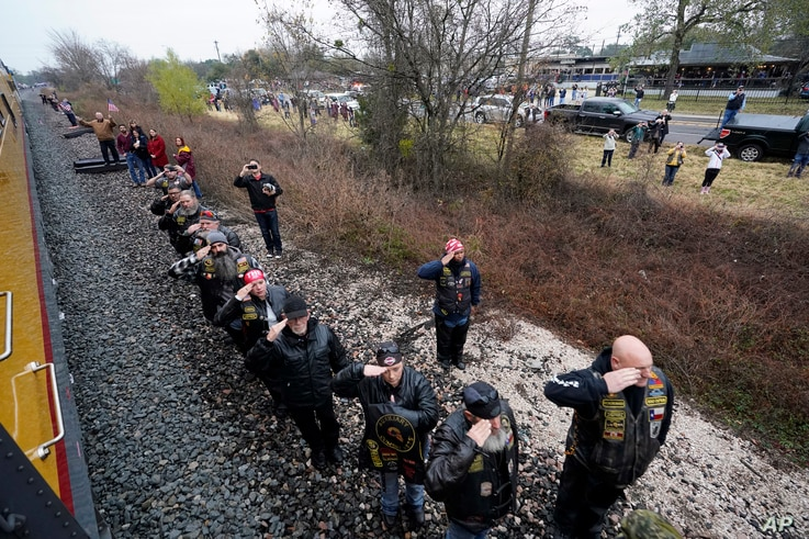 People pay their respects as the train carrying the casket of former President George H.W. Bush passes, Dec. 6, 2018, along the route from Spring to College Station, Texas.