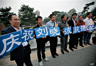 """Supporters of Liu Xiaobo hold cards that read """"We celebrate Liu Xiaobo winning the Nobel Prize"""" outside a park in Beijing, China, 08 Oct. 2010"""