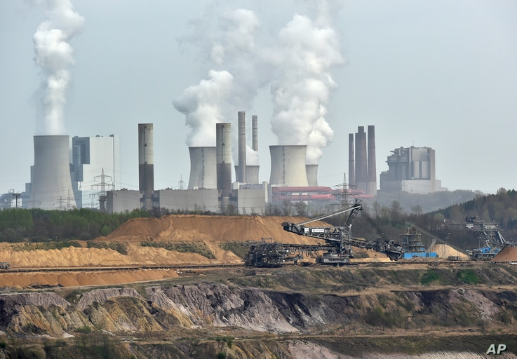 FILE - Giant machines dig for brown coal at the open-cast mining Garzweiler in front of a power plant near the city of Grevenbroich, Germany, April 3, 2014.