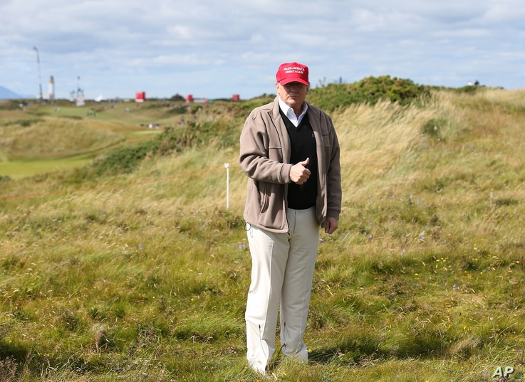 Donald Trump gestures to the media on the Turnberry golf course in Turnberry, Scotland, July 30, 2015.