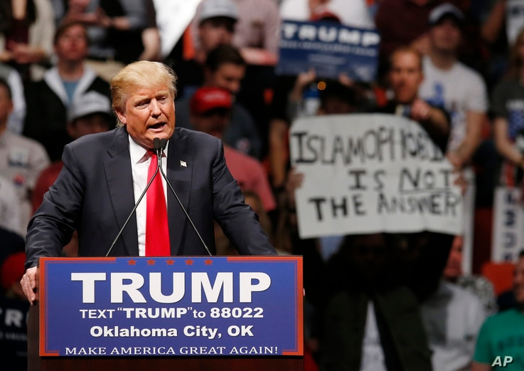 "FILE - Republican presidential candidate Donald Trump speaks at a rally as a man holds up a sign that reads ""Islamophobia is not the answer"" in Oklahoma City, Feb. 26, 2016."