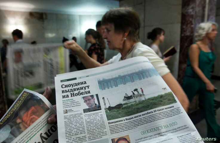 An employee distributes newspapers, with a photograph (L) of former U.S. spy agency contractor Edward Snowden seen on a page, at an underground walkway in central Moscow, July 2, 2013.