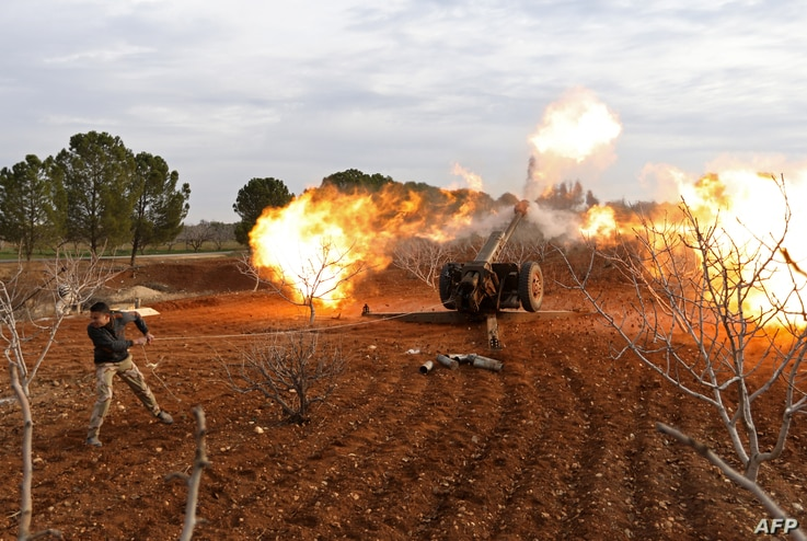 An opposition fighter fires a gun from a village near al-Tamanah during ongoing battles with government forces in Syria's Idlib province on Jan. 11, 2018.
