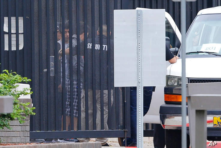 Authorities move immigrant children into a van from a youth holding facility to an undisclosed location, July 10, 2018, in Phoenix.