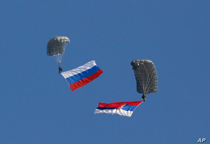 FILE - Serbian soldiers parachute from a Mi-8 transport helicopter with a Russian, left, and Serbian flags during joint Russian-Serbian military exercices at Nikinci training ground, 60 kilometers west of Belgrade, Serbia, Nov. 14, 2014.