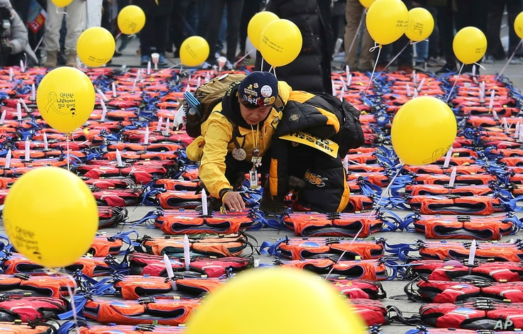 FILE - An unidentified mother of a high school student among 304 victims of sunken ferry Sewol in 2014 places a light stick on a life vest symbolizing the victims before a candle light vigil in Seoul, South Korea, Jan. 7, 2017.