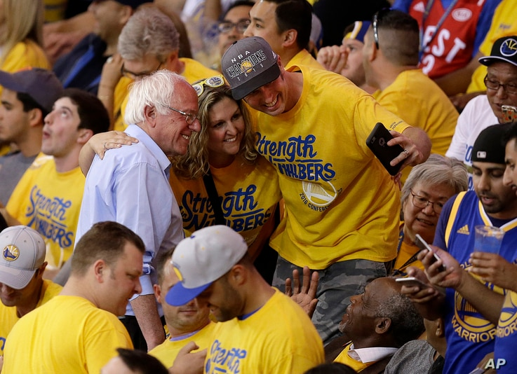 Democratic presidential candidate Senator Bernie Sanders, left, has his photo taken with fans during the second half of Game 7 of the NBA basketball Western Conference finals between the Golden State Warriors and the Oklahoma City Thunder in Oakland,...