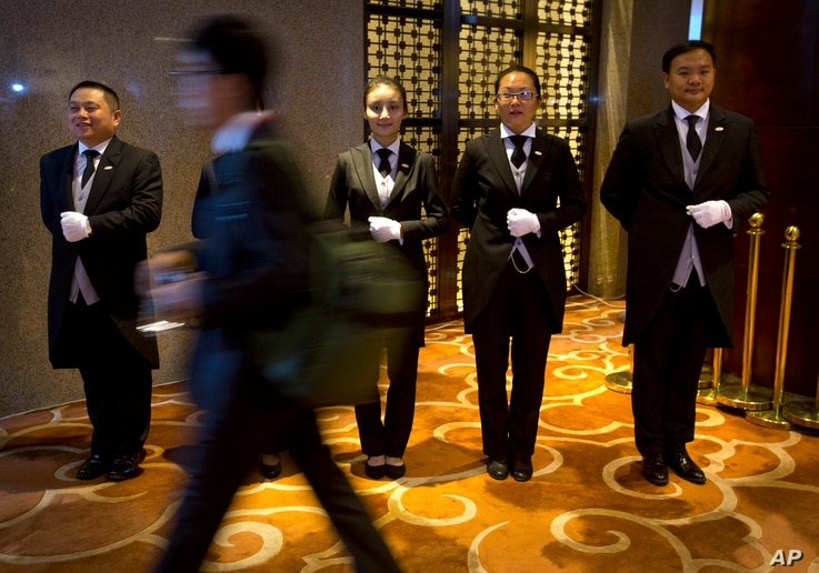 In this Sept. 25, 2015 photo, Chinese butler school graduates stand at attention outside the entrance to a conference in Beijing. A butler is a new must-have for some of China's super-rich.