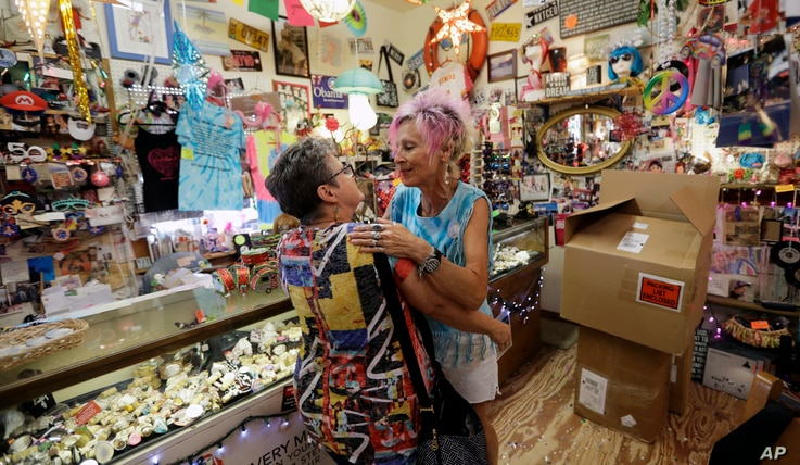 Owner Sally Marco, right, greets a customer is at her shop, Gratitude, in Port Aransas, Texas, Sept. 30, 2017.