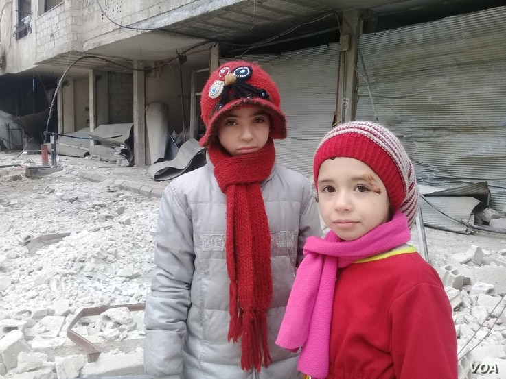 Nour and Alaa stand in the rubble of their hometown in Eastern Ghouta, Feb. 23, 2018.