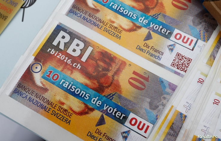 """FILE - Promotional leaflets for the """"Unconditional Basic Income"""" are pictured on the Plainpalais square in Geneva, Switzerland, May 14, 2016. Swiss voters determine the referendum's outcome Sunday."""