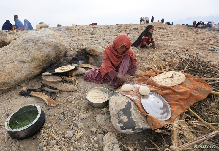 An internally displaced Afghan woman who fled from recent conflict cooks bread outside a shelter in Khogyani district of Nangarhar province, Afghanistan. Nov. 28, 2017.