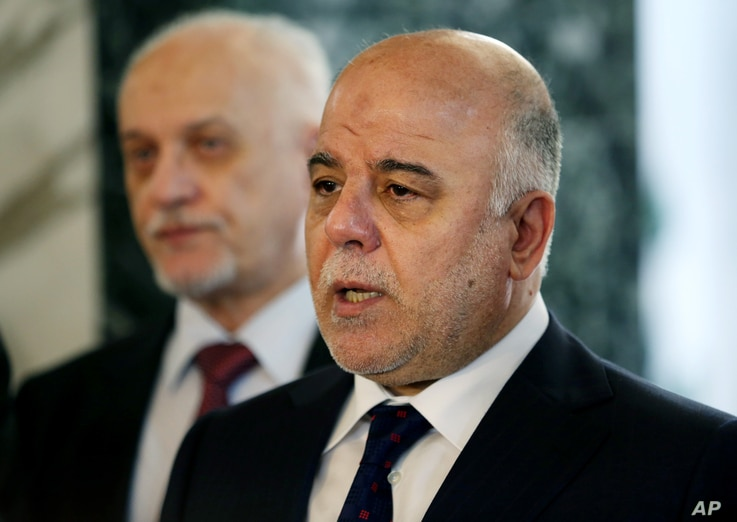 Iraqi Prime Minister Haider al-Abadi, right, holds a new conference before leaving to the United States at Baghdad airport, April 13, 2015.