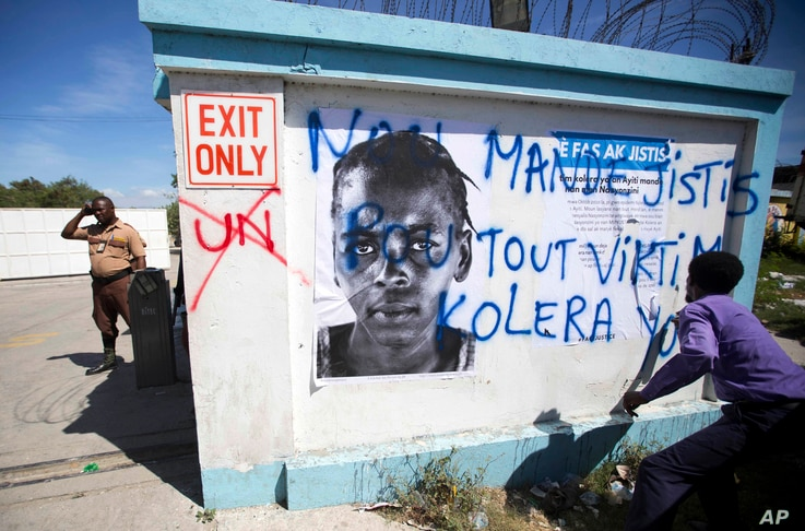 """A demonstrator spray paints the message in Creole """"We demand justice for all cholera victims"""" outside United Nations headquarters to protest the U.N. peacekeeping mission in Port-au-Prince, Haiti, Oct. 15, 2015."""