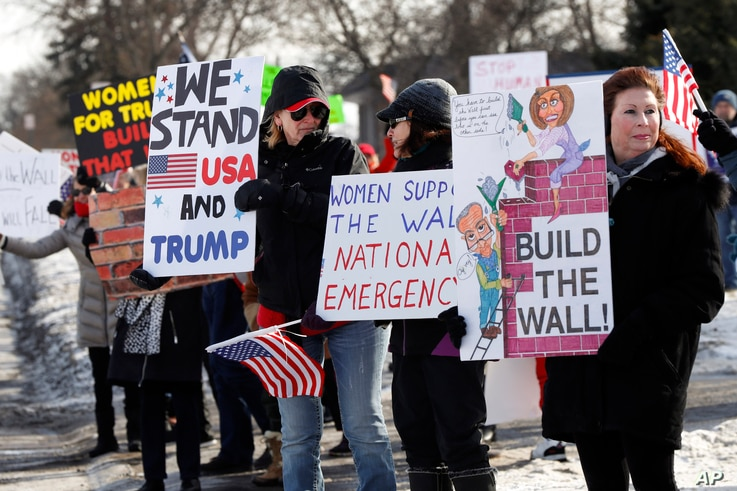 "Supporters hold signs at a Women for Trump ""Build the Wall"" rally in Bloomfield Hills, Mich., Jan. 26, 2019."
