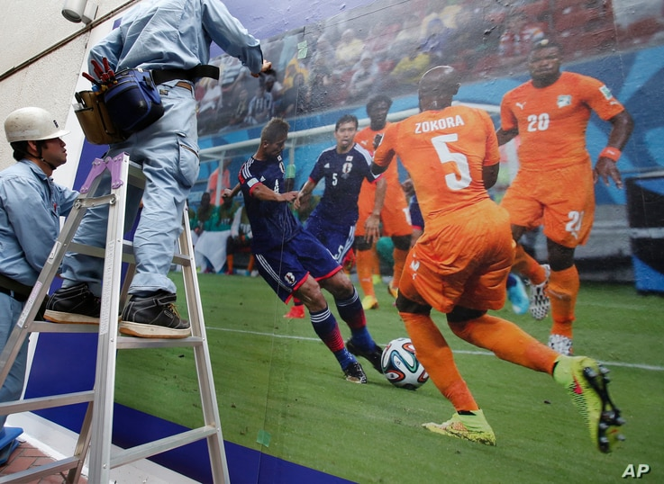 A worker atop a step ladder place a sheet of a blown-up photograph of a World Cup match in which Japan played against Ivory Coast, on the wall as another worker assists him at Shibuya shopping district in Tokyo, Monday, June 16, 2014. (AP Photo/Shizu