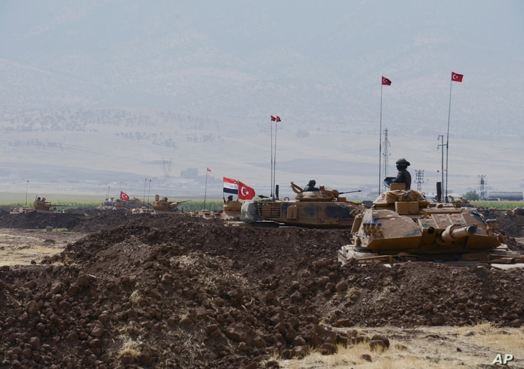 Turkish and Iraqi soldiers sit on Turkish tanks during the exercises in Silopi, near the Habur border gate with Iraq, southeastern Turkey,  Sept. 26, 2017.