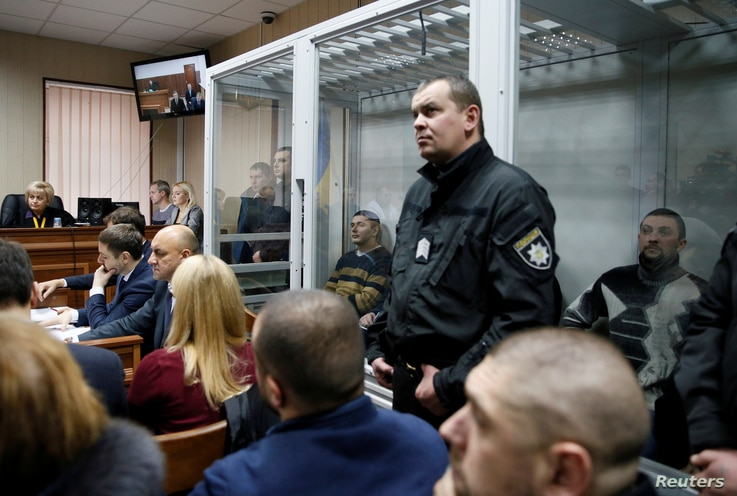 Former riot police officers, suspected of killing protesters during the Maidan revolt of 2014, sit inside a glass-walled room during a court hearing in Kyiv, Ukraine, Monday, Nov. 28, 2016.