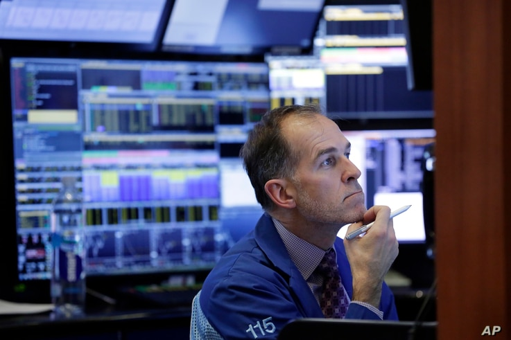 Trader Mark Puetzer works in a booth on the floor of the New York Stock Exchange, March 22, 2018. Stocks fell sharply and bond prices rose after the Trump administration moved to place tariffs on some goods imported from China and restrict Chinese in...