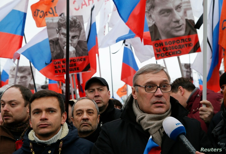 Opposition leader and Russia's former Prime Minister Mikhail Kasyanov, right, speaks to the media with opposition activist Ilya Yashin, left, during a march to commemorate Kremlin critic Boris Nemtsov, who was shot dead Friday, in Moscow, March 1, 20...