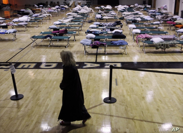 A person walks through a makeshift shelter in a gymnasium at Toms River East High School as they arrive to vote Tuesday, Nov. 6, 2012, in Toms River, N.J.  N.J. Voter turnout was heavy in several storm-ravaged Jersey Shore towns, with many voters exp