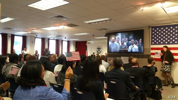 "A hundred immigrants, from 31 countries, join in singing ""America, the Beautiful"" after becoming naturalized U.S. citizens. (M. Cuevas/VOA)"