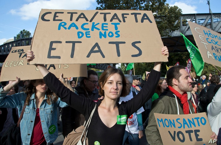 "CETA Trade Deal: A protester holds a placard which reads, ""CETA/TAFTA steel our States"" during a rally to protest against the trade deals with Canada and the U.S. in Paris, Saturday, Oct. 15, 2016."