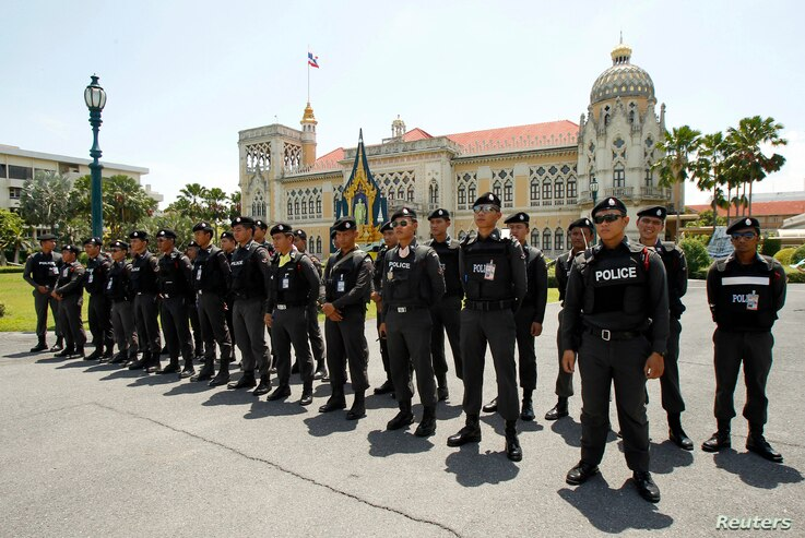 Policemen stand guard at the Government House during an anti-government protesters' rally in Bangkok May 9, 2014. Thai police fired teargas on Friday at royalist protesters bent on bringing down a caretaker government after a court threw Prime Minist