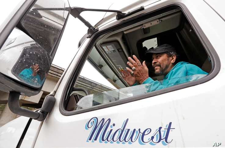 Charles McCaskill, a trucker heading to Nebraska to deliver frozen salmon, talks from the cab of his truck while parked while waiting for Interstate 90 to reopen, Jan. 18, 2017, in North Bend, Wash.