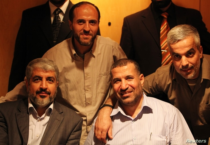 Top commander of Hamas armed wing Al-Qassam brigades, Ahmed Al-Jabari, front right, with Hamas leader Khaled Meshaal, front left, and Palestinians freed in a prisoner swap between Hamas and Israel, Cairo, October 18, 2011.