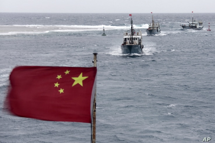 In this photo taken on Friday, July 20, 2012, Chinese fishing boats sail in the lagoon of Meiji reef off the island province of Hainan in the South China Sea.
