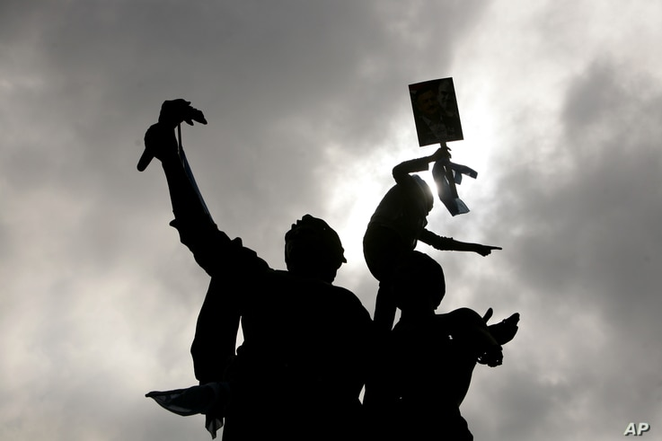 A Lebanese protester gestures from the top of the monument at Martyrs' Square as the crowd begins to gather for the funeral of the country's intelligence chief, Brig. Gen. Wissam al-Hassan in Beirut, Lebanon, Sunday, Oct. 21, 2012.