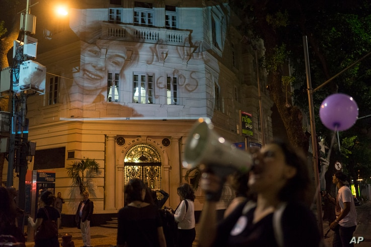 A photo of Lucia Perez,16, who was rapped and killed in Argentina, is projected on a building as women participate in a demonstration against gender violence in Rio de Janeiro, Brazil, Oct. 25, 2016.
