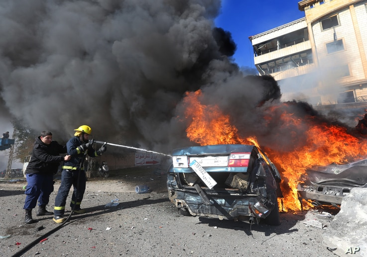 Lebanese firefighters extinguish a burned car at the site of an explosion, in the suburb of Beir Hassan, Beirut, Lebanon, Wednesday Feb. 19, 2014. A blast in a Shiite district in southern Beirut killed at several people on Wednesday, security officia