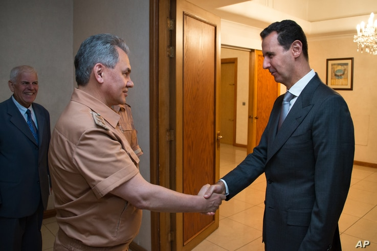 Syrian President Bashar al-Assad shakes hands with Russian Defense Minister Sergei Shoigu in Damascus, June 18, 2016.